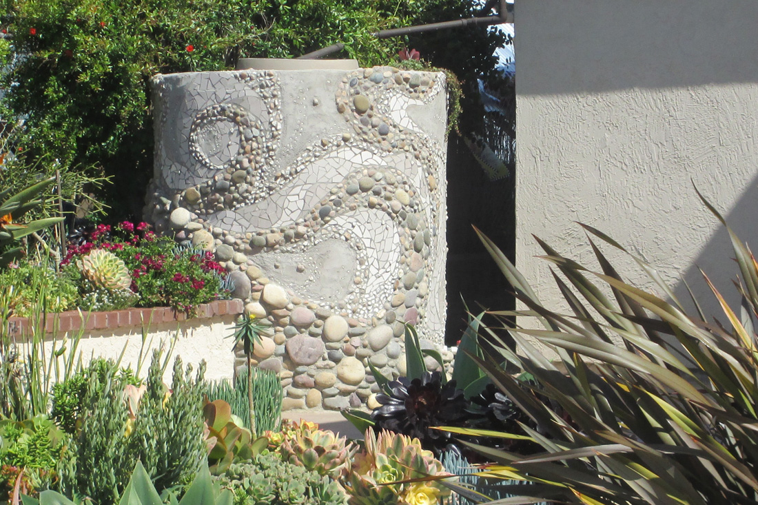Rainwater collection tank covered in mosaic by Alex Miller.